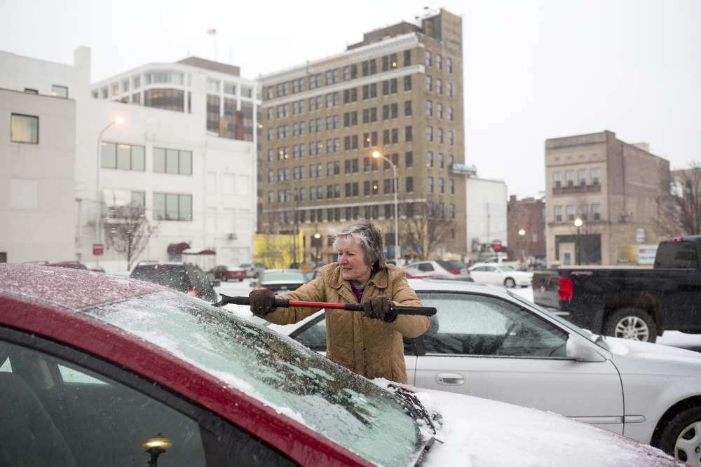 Jill Goldsmith scrapes ice off her car's windshield Monday, Dec. 28, 2015, in Jackson, Mich. The National Weather Service issued a winter storm warning until Tuesday morning. (Nick Gonzales | Mlive.com)