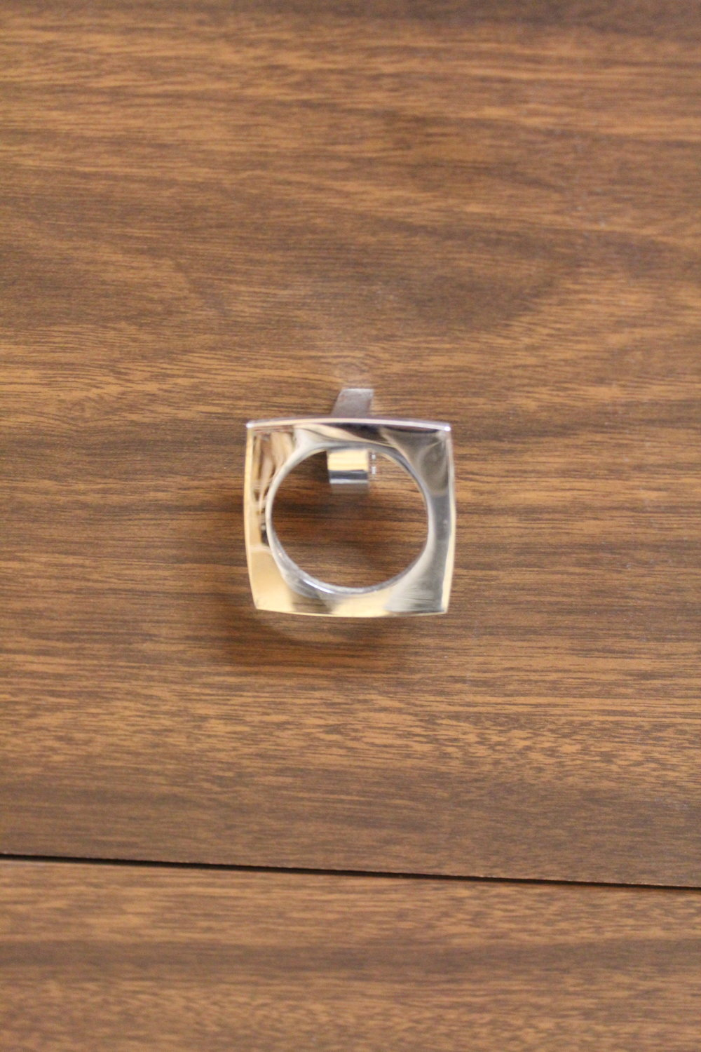 Silver square drawer pull on midcentury modern bureau