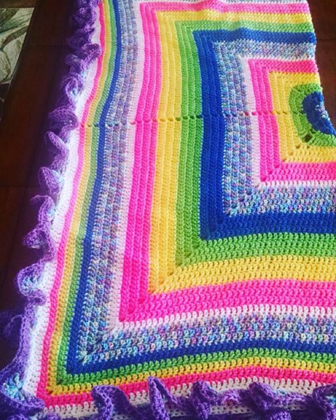 "This is a handmade afghan made by laynefaire. This hand crocheted afghan measures approximately 50"" square. Made of worsted weight acrylic yarn, the afghan is comprised of increasing layers of squares in royal blue, spring green, sun yellow, carnation pink, white and pastel variegated, and trimmed in purple.  As fun and uninhibited as the man who inspired it, the proceeds from this charity auction will benefit Switchboard, the charity chosen for Harry Styles' 22nd birthday fandom charity drive.  International bidders - please note that due to the heavy weight of the afghan, shipping will be around $41!  http://www.ebay.com/itm/-/281895282145?  Happy Bidding!"