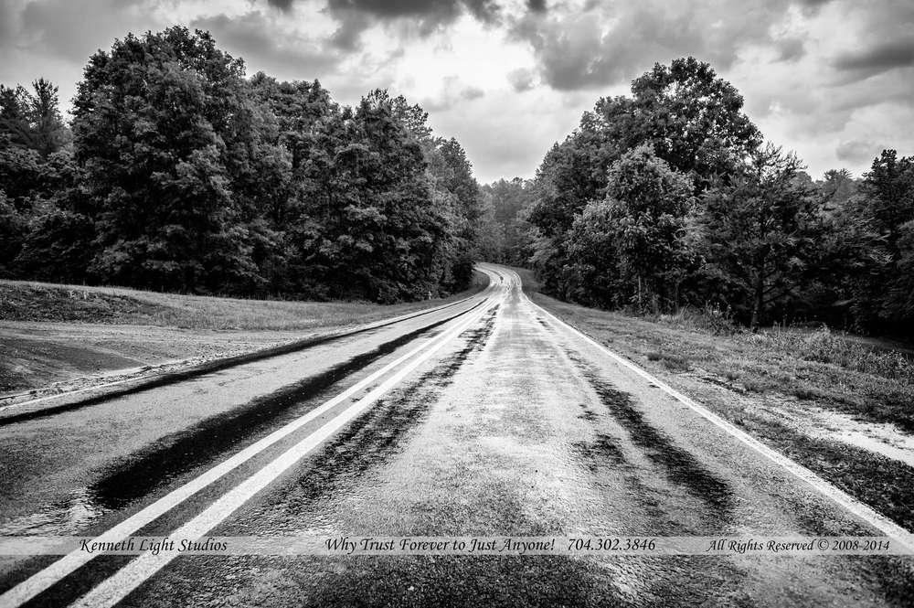 In black and white, I love the contrast with rain black and clouds being black and white, trees fussy shades and the road just winds to the distance better in black and white for some reason.