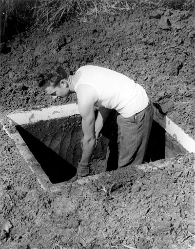 Lewis Hartman digs an outhouse pit as part of a hookworm eradication program. Civilian Public Service camp #141, Gulfport Mississippi, 1946.  Photo Credit: From the private collection of Leo Harder, licensed under Creative Commons Attribution Share-Alike 2.5.