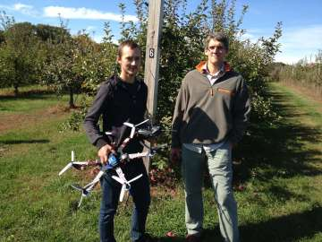 University of New Hampshire doctoral student Matt Wallhead (left) and assistant professor of plant pathology Kirk Broders with the unmanned aerial vehicle they're developing to help apple farmers survey for disease and fungus.  Credit: Rachel Rohr. Image Source.