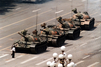 """Tank Man"" temporarily stops the advance of a column of tanks on June 5, 1989, in Beijing. This photograph (one of four similar versions) was taken by Jeff Widener of the Associated Press. (Source: Wikipedia)"