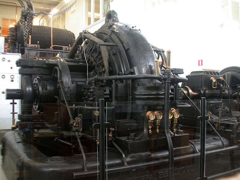 ALEXANDERSON ALTERNATOR IN THE GRIMETON VLF TRANSMITTER. THE DRIVE MOTOR IS AT THE EXTREME RIGHT; THE SPEED-INCREASER GEARBOX IS JUST TO ITS LEFT. NOTE THE BRONZE-COLORED SHAFT COUPLING. IMAGE AND CAPTION COURTESY GUNTHER TSCHUCH AND WIKIMEDIA COMMONS.
