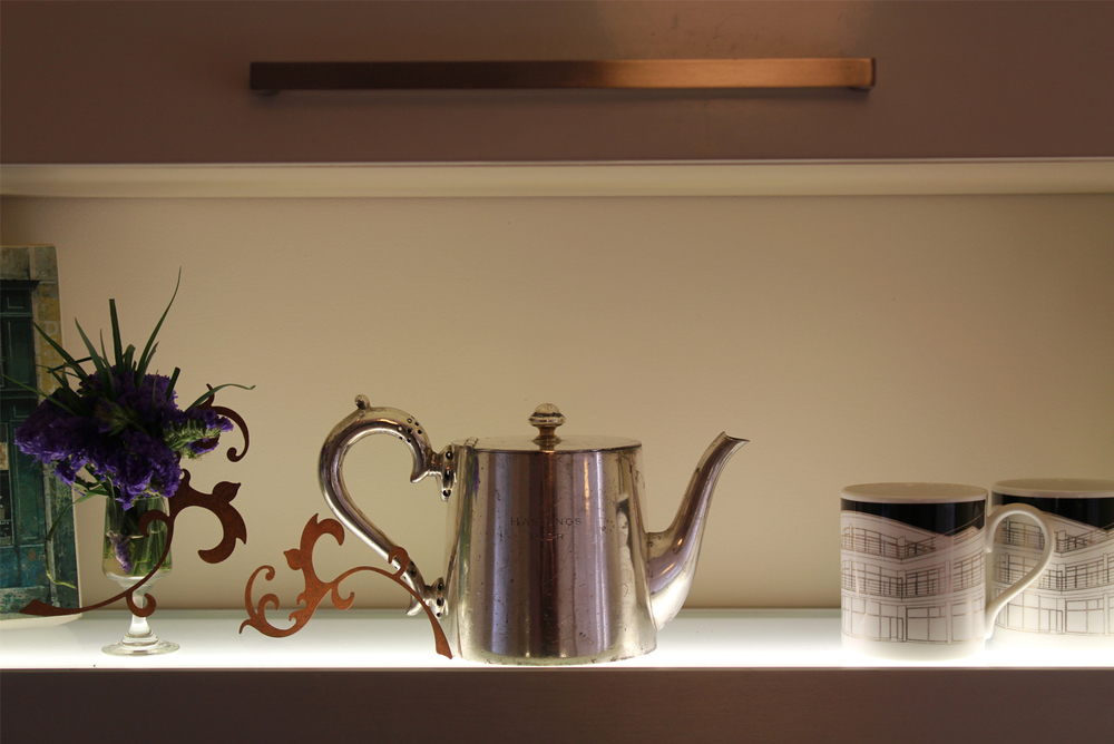 Hastings Pier silver plated tea pot with De La Warr pavilion mugs on light shelf with core 10 laser cut decorations.