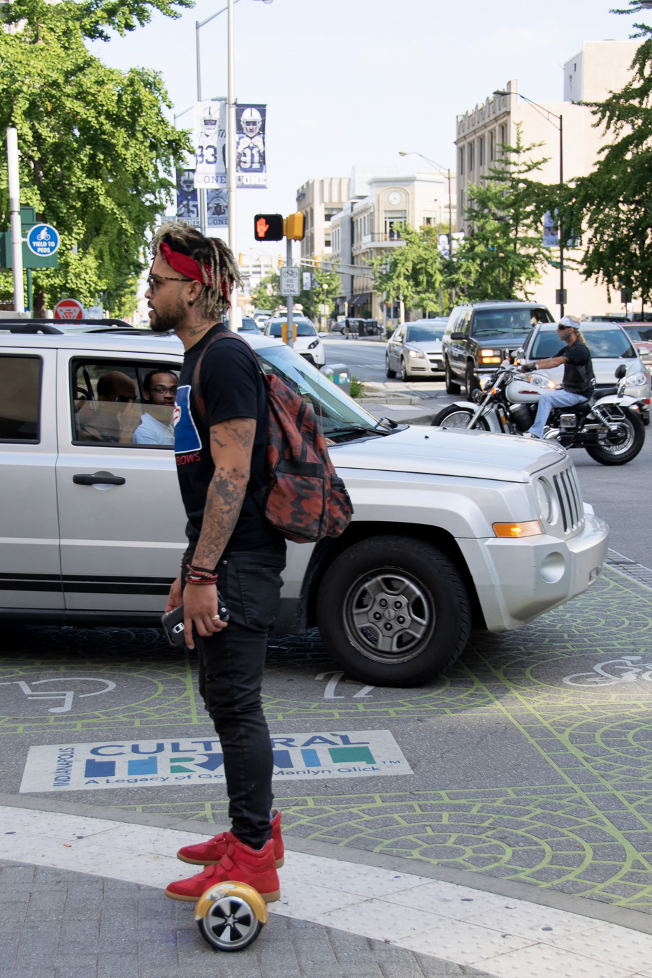 A guy crosses the street on his Swagway Scooternext to a gasoline-eating car and a motorcycle.