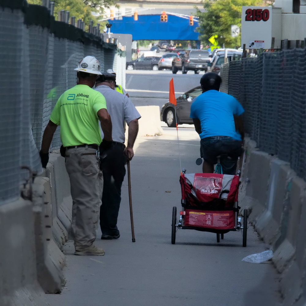 The guy in the blue shirt was pulling a bike trailer. He was in a hurry and when he passed me I was surprised to see a baby inside. What an exciting ride for the baby!