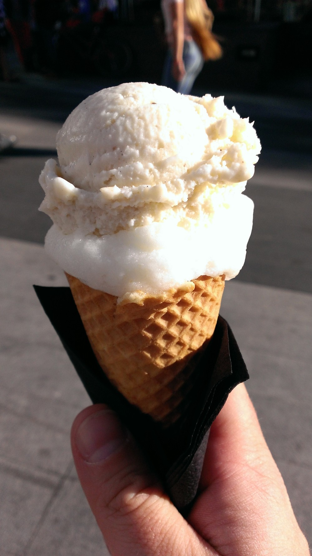 A waffle cone with coconut ice cream and lemon sorbet
