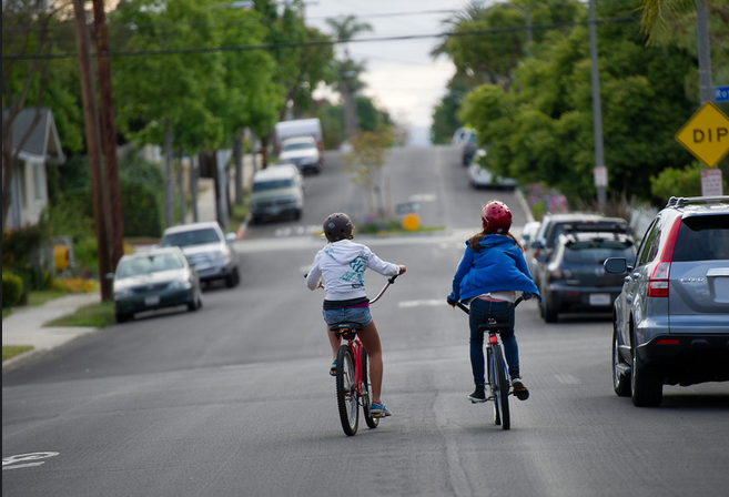 Two young girls on the Vista Bike Blvd. in Long Beach riding home from school. With the new law going into effect September 16th motorists will need to give bicyclists a space of at least three feet when passing. Image by Allan Crawford.