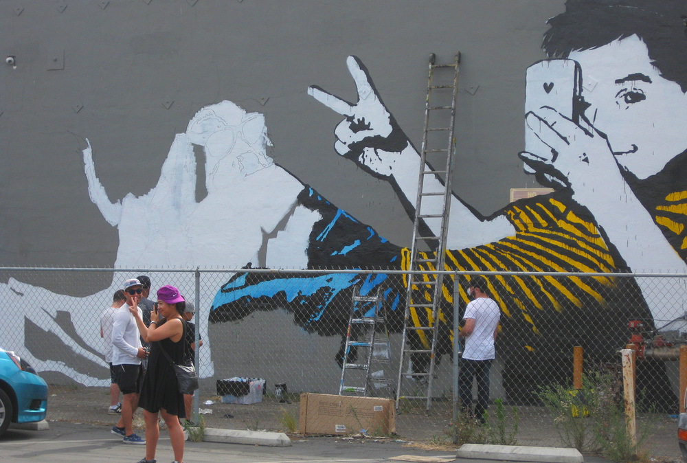 A visitor poses in front of the BumbleBee street art team painting a mural for Pow Wow Long Beach at Berlin Bistro in the East Village.