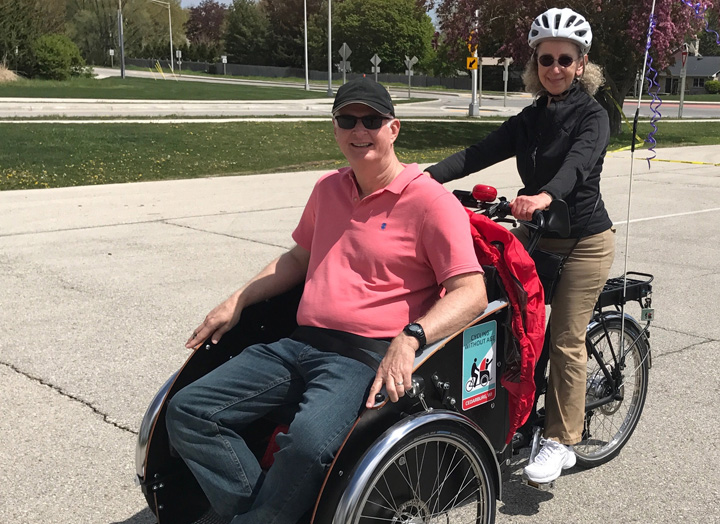 Kit Keller takes _ for a ride on an electric cargo bike as part of the Cedarburg WI _ program.