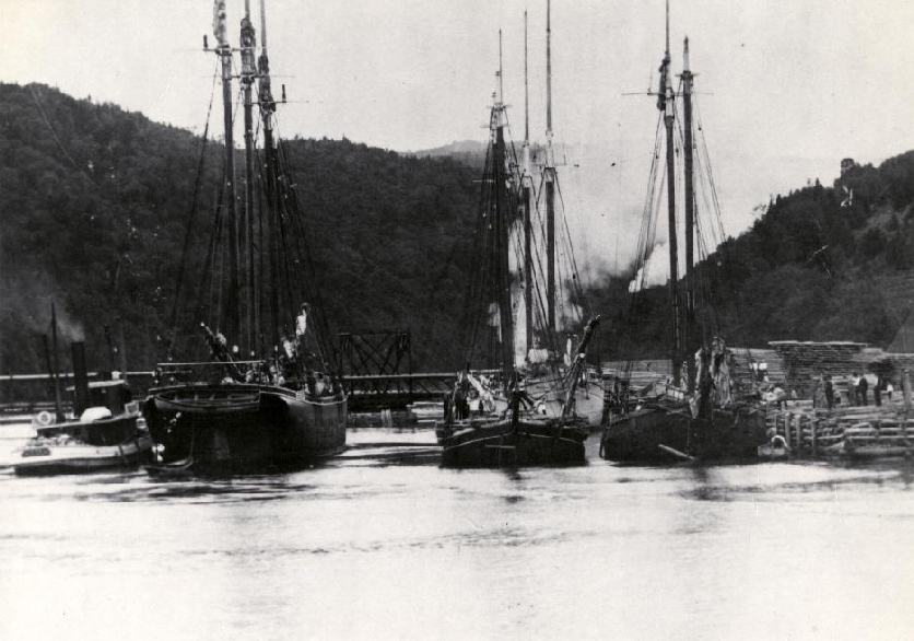 This view of the harbour in Alma shows the tugboat Stadium lining up three vessels at the dock. The vessels would be tied together at the dock before the tide went out. The vessels had to be tied together because the dock is so small. When the tide was out the vessels would rest on the ocean floor.
