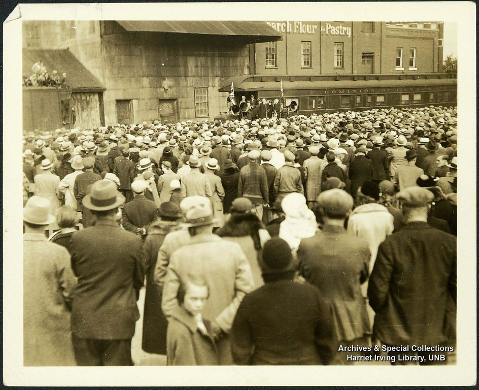 A very large crowd of people gathered to hear one of R.B. Bennett's campaign speeches delivered from the back of a train. This type of 'whistle-stop' campaigning was an effective way to reach many people at the time.