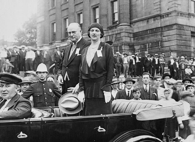 R.B. Bennett and his sister Mildred standing in a car during the 1930 election campaign. Mildred was of tremendous help during the campaigns.