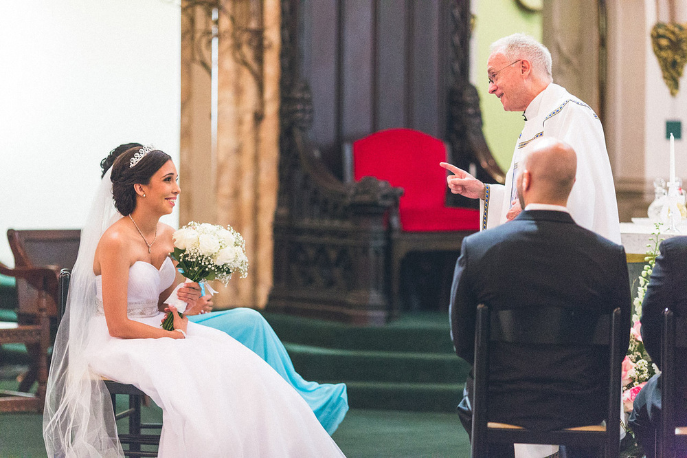 Bride laughs with Priest