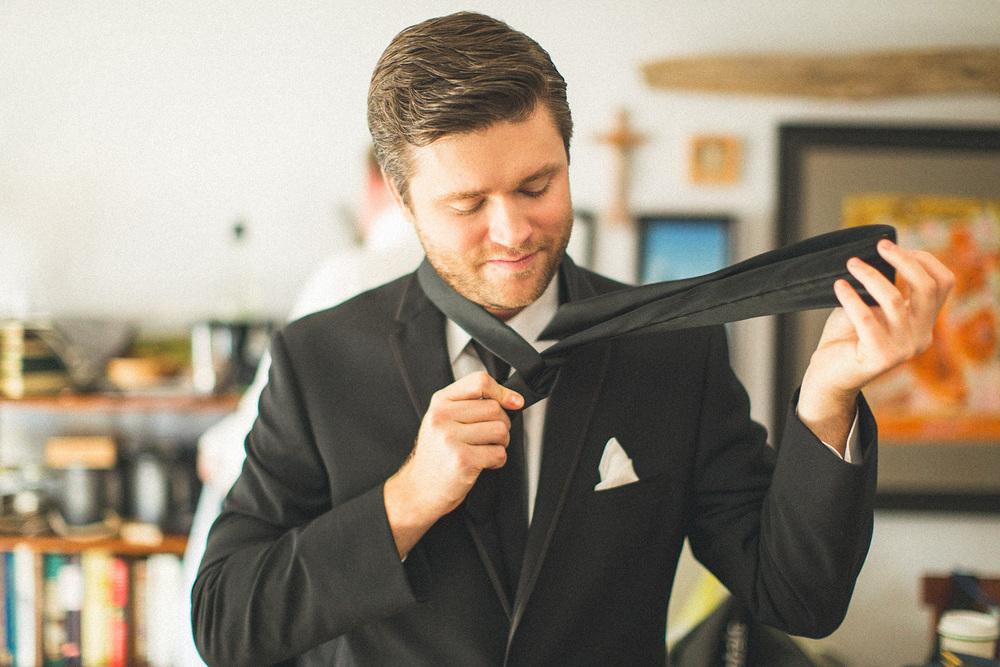 Groomsman puts on Tie