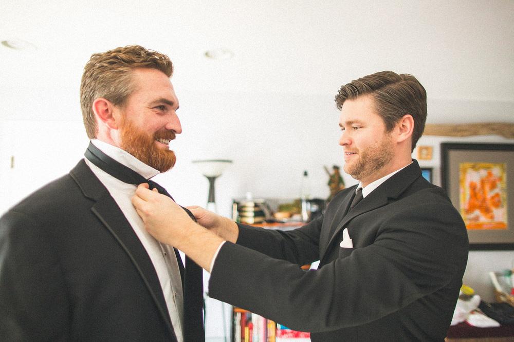 Groomsman helps with tie