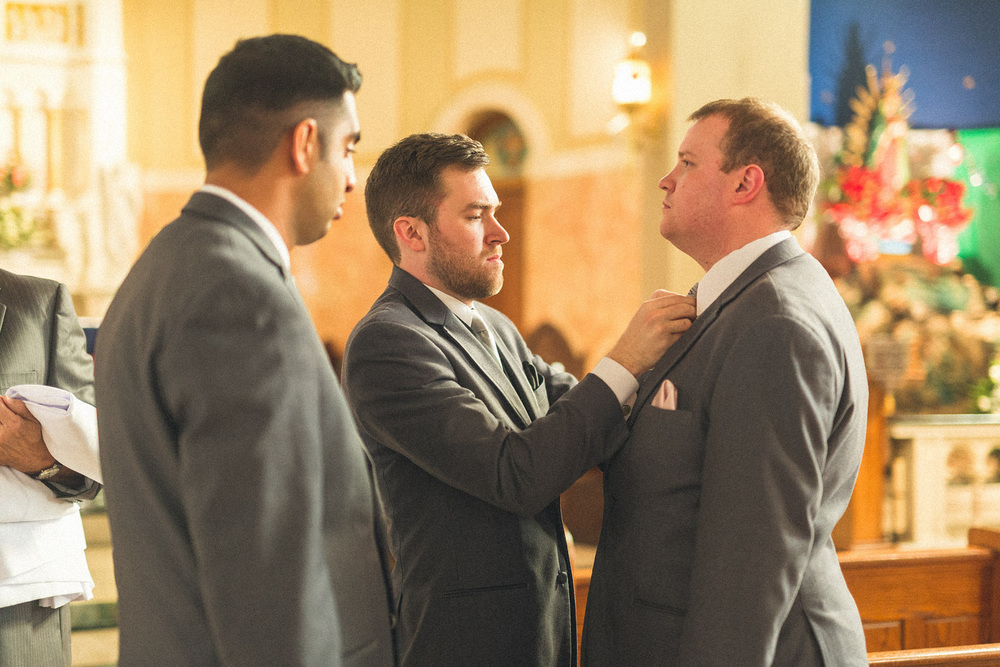 Groom gets tie adjusted