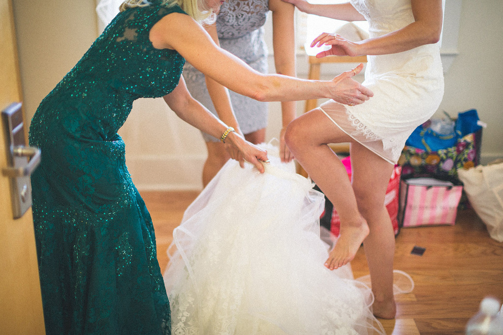 Mom helps bride into dress