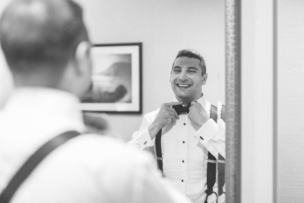 Groom adjusts bow tie