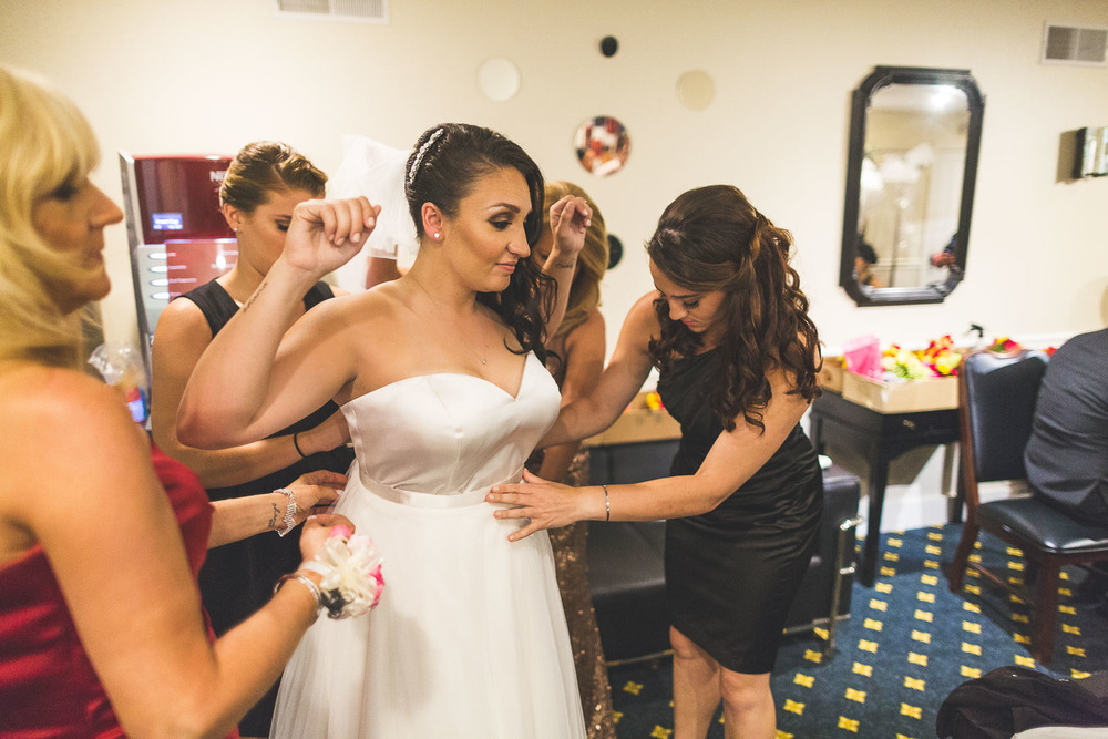Sister helps with brides dress