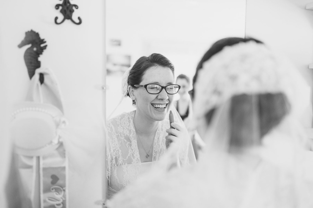 Bride applying lipstick laughing