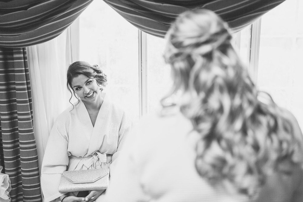 Bridesmaid looks at Bride while getting ready