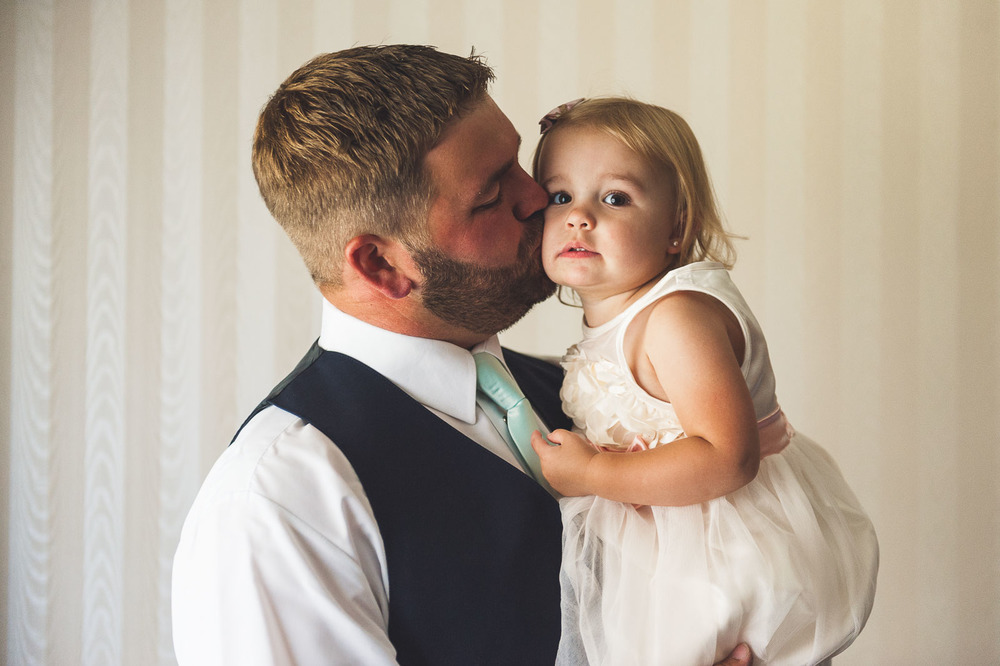 Flower girl gets a kiss from dad