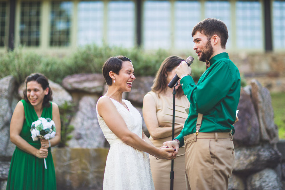 Groom making bride laugh with vows
