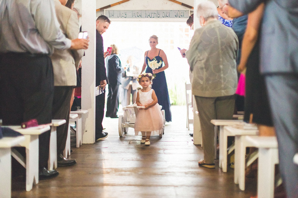 Flower girl walks down with sister in wagon