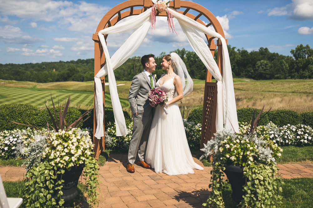 Bride/Groom stand under arch