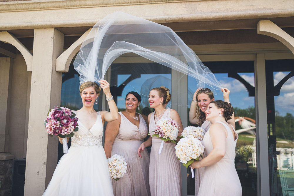 Bridesmaids hide under vail