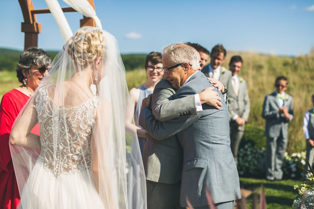 Father of bride hugs groom