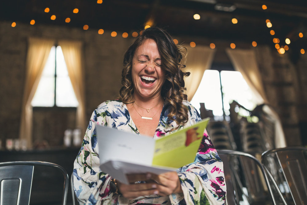 Bride laughs at card from groom