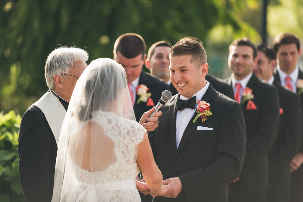 Groom smiles during vows
