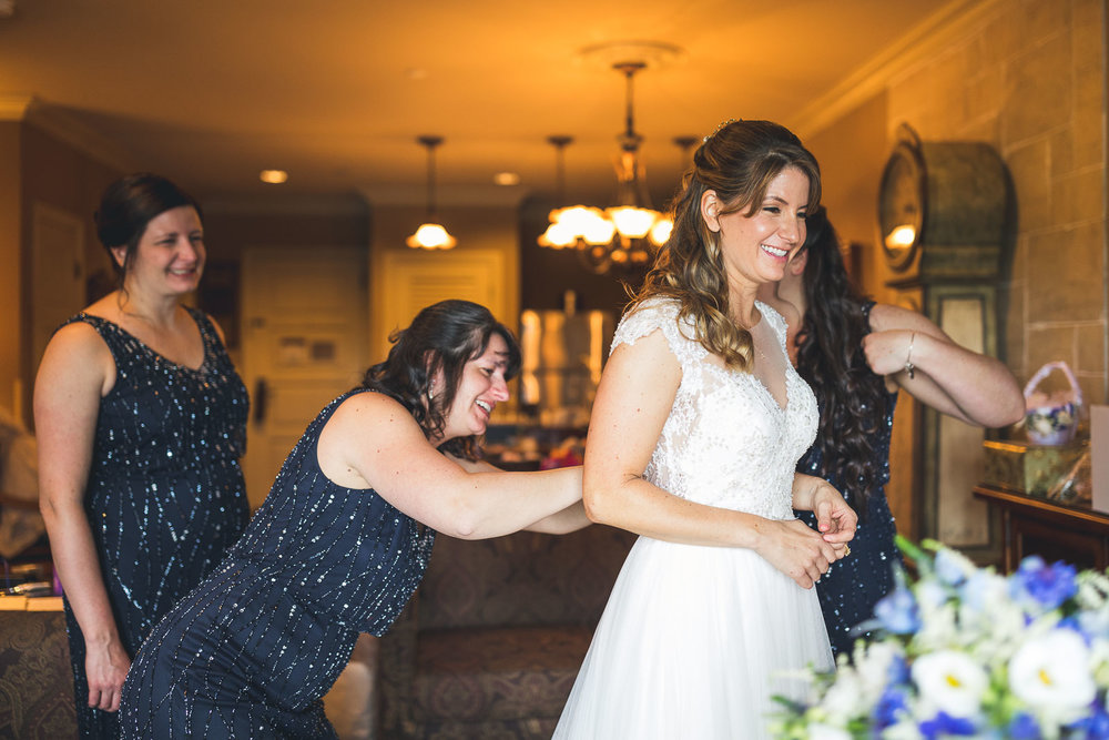Bride gets help with dress from sisters.