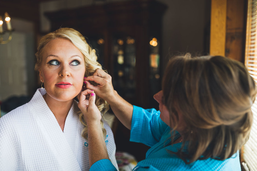 Bride gets ear rings put on