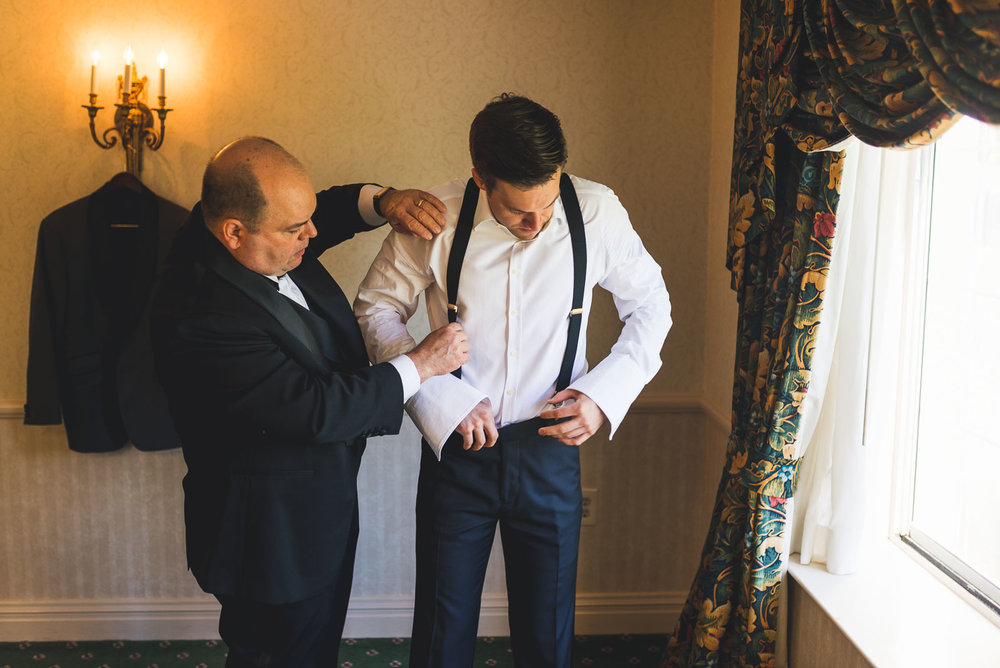 Father helps bride with suspenders