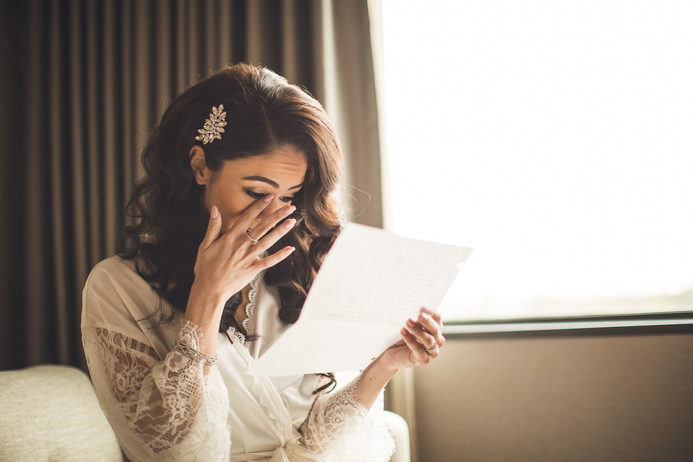 Bride wipes tear reading letter from groom