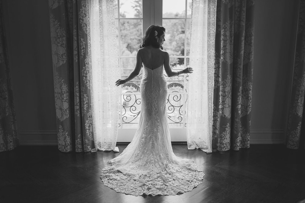Bride looks out window