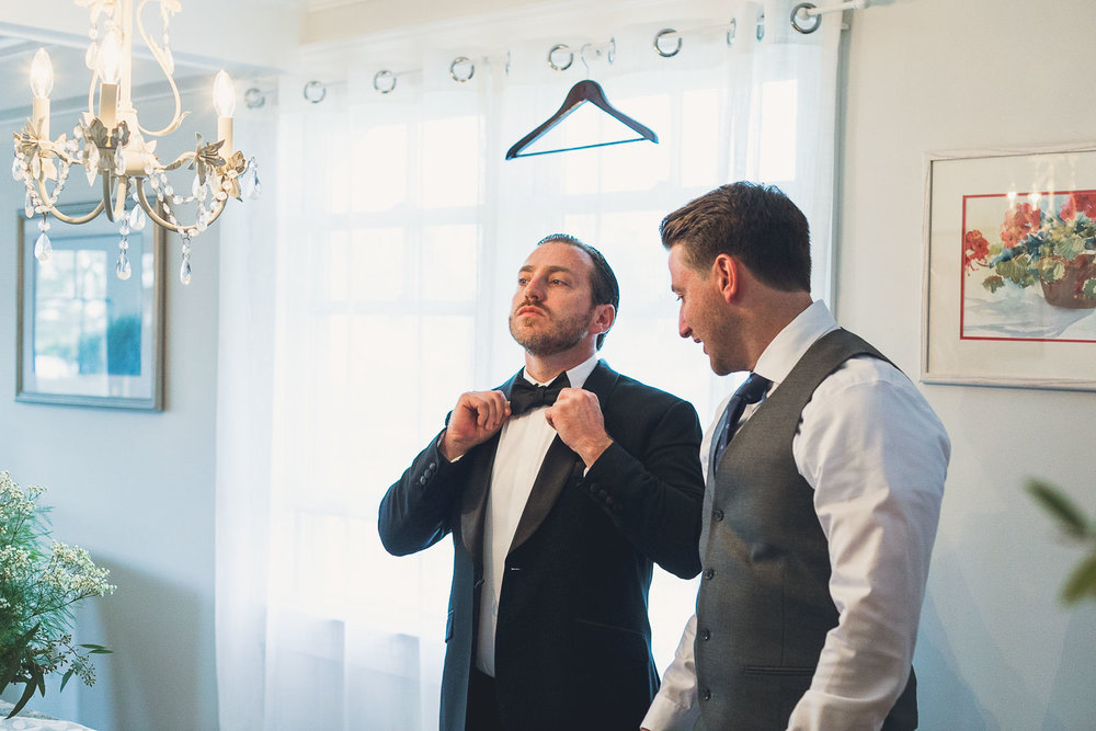 Groom adjusts tie