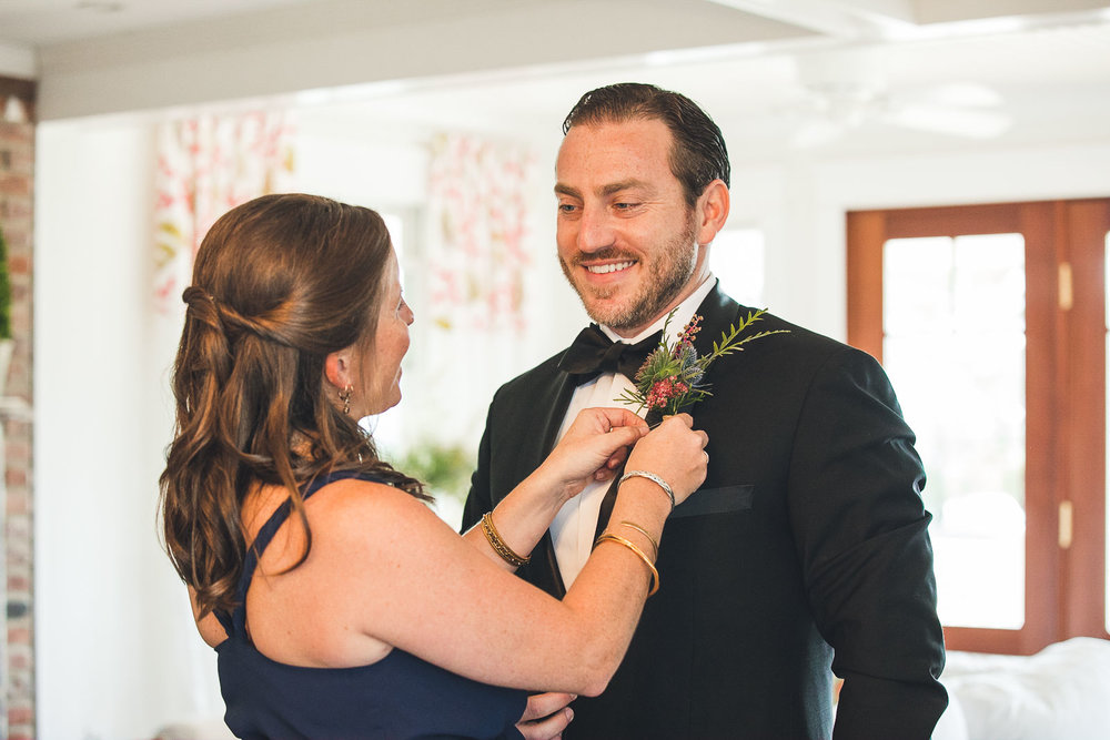 Bride sister helps groom with boutonniere