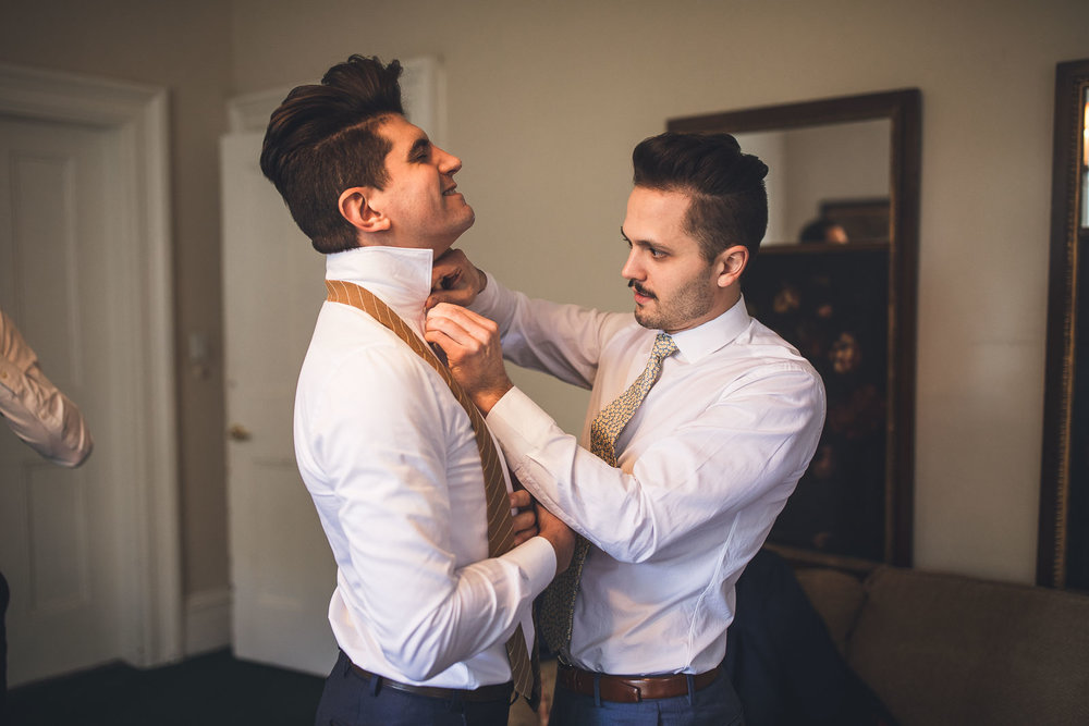 Groom helps brother with shirt