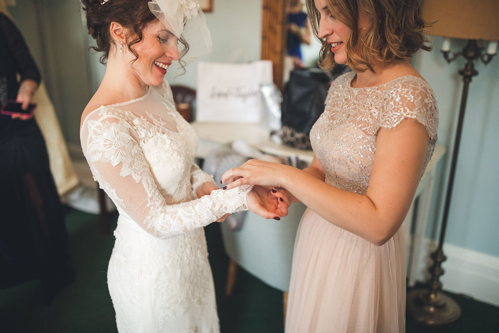Sister helps bride with dress