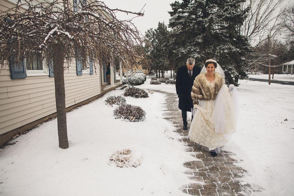 Bride walks to car on snowy wedding day