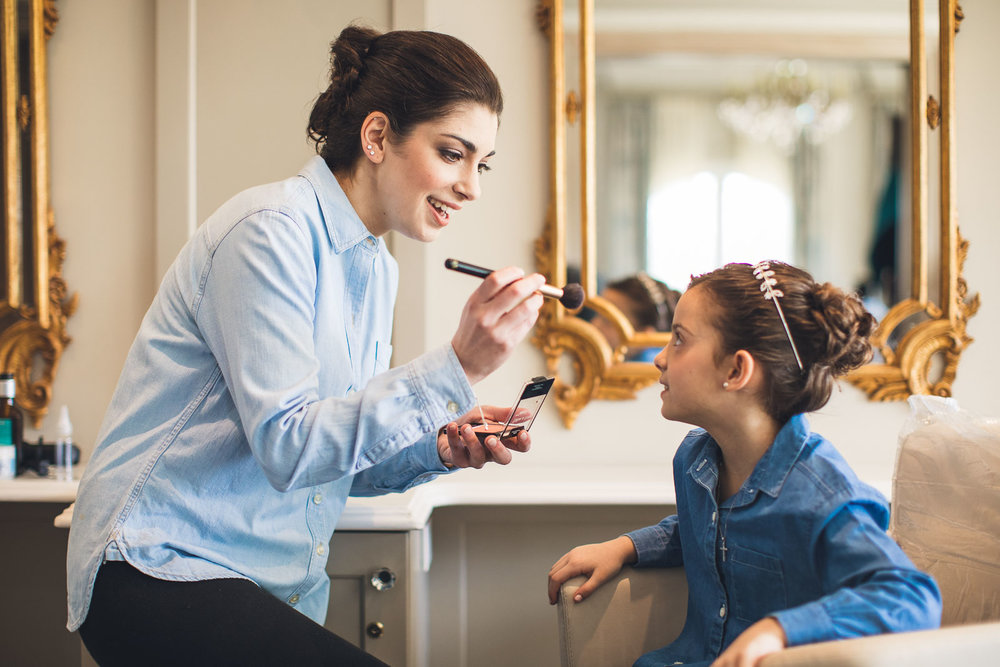 Bride helps flower girl with makeup