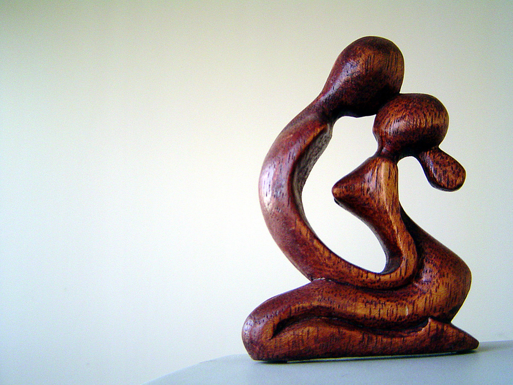 Article: Why Are Soul Contracts So Painful? Photo: A wooden statue of a man and woman sitting and their forehead's touching.