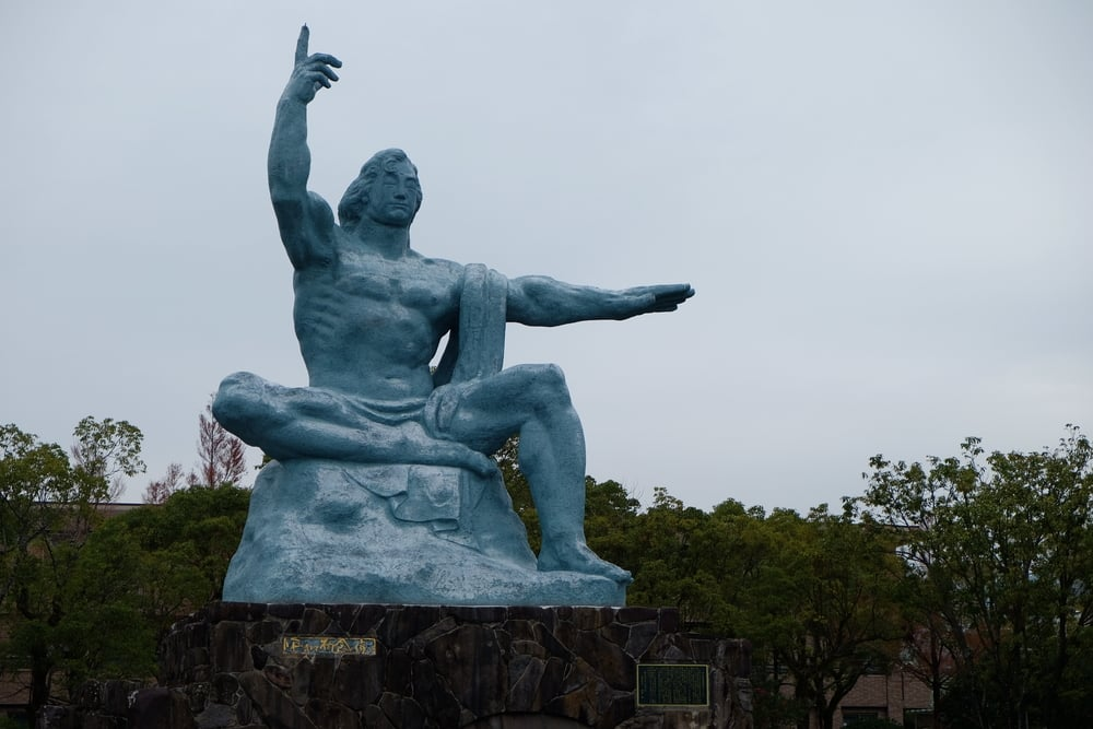 The Peace Statue in Nagasaki, built ten years after the explosion of the atomic bomb there. As explained by the nearby interpretive sign: the elevated right hand points to the threat of nuclear weapons, the outstretched left hand symbolizes tranquility and world peace, the folded right leg symbolizes quiet meditation, the left leg is poised for action in assisting humanity, a prayer for the repose of the souls of all war victims is expressed in the closed eyes, and divine omnipotence and love are embodied in the sturdy physique and gentle countenance of the statue.