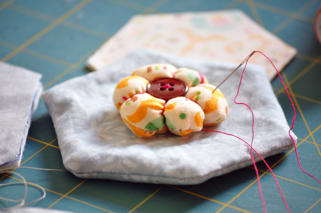 sew the flower pincushion on the top of one big hexagon, covering the hole.
