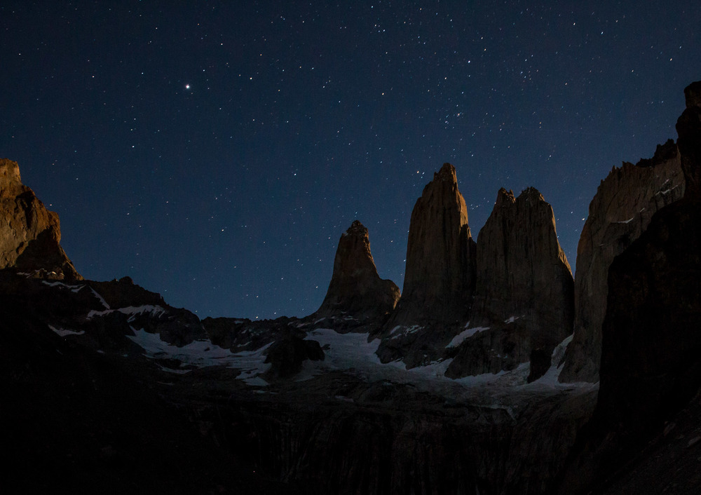 An hour before sunrise, with a full moon just setting providing an outlining glow of the Torres del Paine.